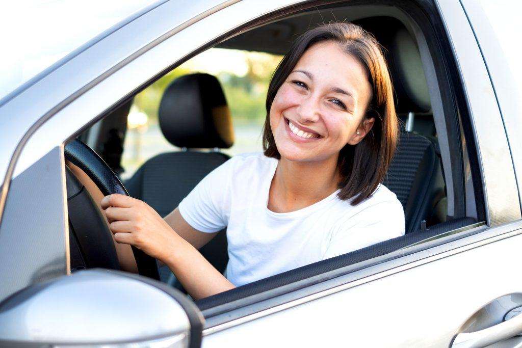Freundlich lächelnde ambulante Pflegekraft in ihrem Auto.
