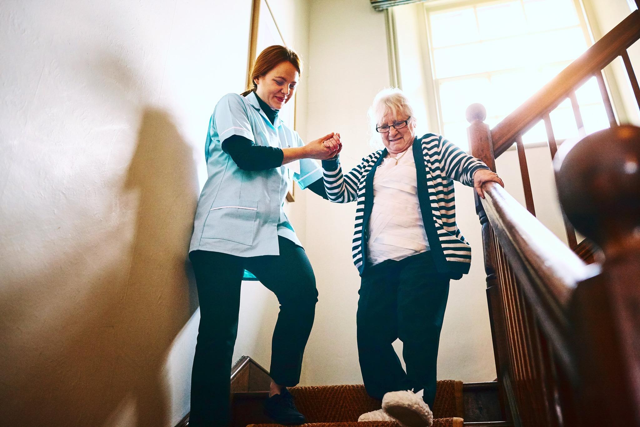 Eine Pflegerin hilft einer älteren Damen beim Treppen runterlaufen.