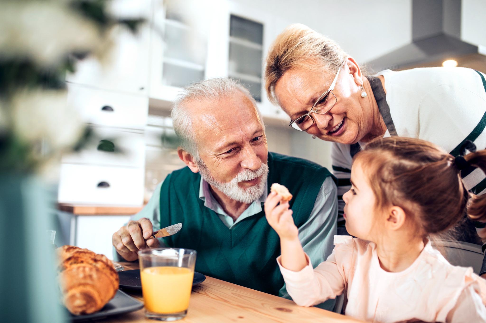 Ein Kind sitzt am Frühstückstisch mit seinen Großeltern.