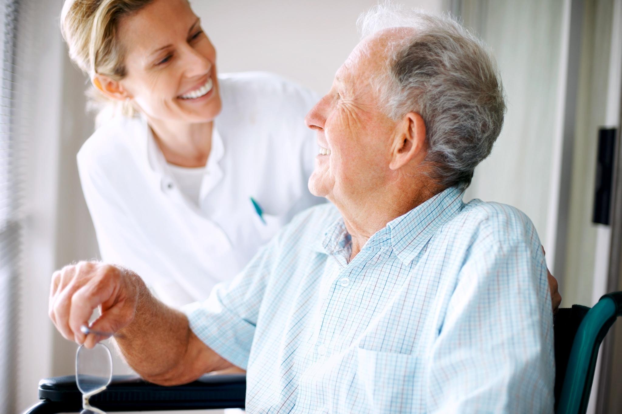Pflegerin und ein älteren Mann lächeln sich an.