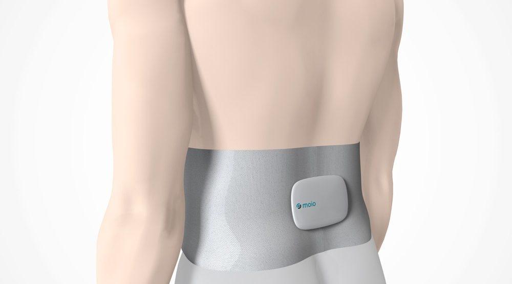Das moio.care Sensormodul mit dem Bauchband am Rücken eines Patienten.